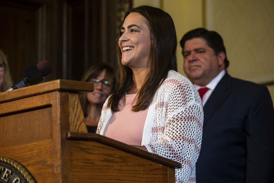 Bentley Stewart, a teacher in the Jacksonville, Illinois, School District 117, speaks Thursday to the benefits of a bill raising the minimum salary for teachers to $40,000 during a bill signing ceremony with Illinois Governor J.B. Pritzker, right, in his office at the Illinois State Capitol.