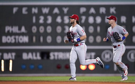 Philadelphia Phillies right fielder Bryce Harper, left, and left fielder Corey Dickerson head to the clubhouse after the team's win over the Boston Red Sox in a baseball game at Fenway Park in Boston, Wednesday, Aug. 21, 2019. The Phillies won 5-2.