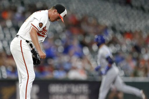 Baltimore Orioles starting pitcher Aaron Brooks, left, reacts after allowing a solo home run to Kansas City Royals' Whit Merrifield, right, during the third inning of a baseball game, Wednesday, Aug. 21, 2019, in Baltimore.