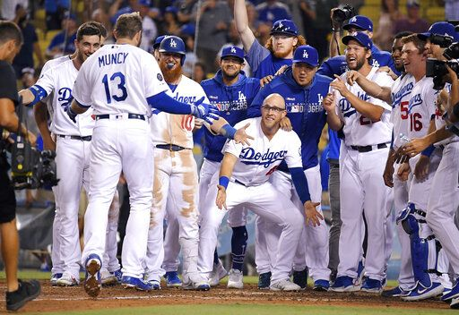 Los Angeles Dodgers wait for Max Muncy to score on a game-ending solo home run during the 10th inning of the team's baseball game against the Toronto Blue Jays on Wednesday, Aug. 21, 2019, in Los Angeles. The Dodgers won 2-1.