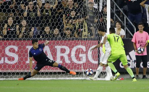 Los Angeles FC forward Carlos Vela, center, scores past San Jose Earthquakes goalkeeper Daniel Vega (17) and defender Nick Lima during the first half of an MLS soccer match Wednesday, Aug. 21, 2019, in Los Angeles.