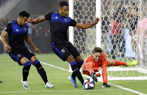 Los Angeles FC goalkeeper Tyler Miller, right, lunges for the ball as San Jose Earthquakes forward Danny Hoesen, center, closes in during the first half of an MLS soccer match Wednesday, Aug. 21, 2019, in Los Angeles.