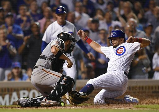 Chicago Cubs' Kyle Schwarber right, is tagged out at home plate by San Francisco Giants catcher Stephen Vogt during the eighth inning of a baseball game Wednesday, Aug 21, 2019, in Chicago. Chicago won 12-11.