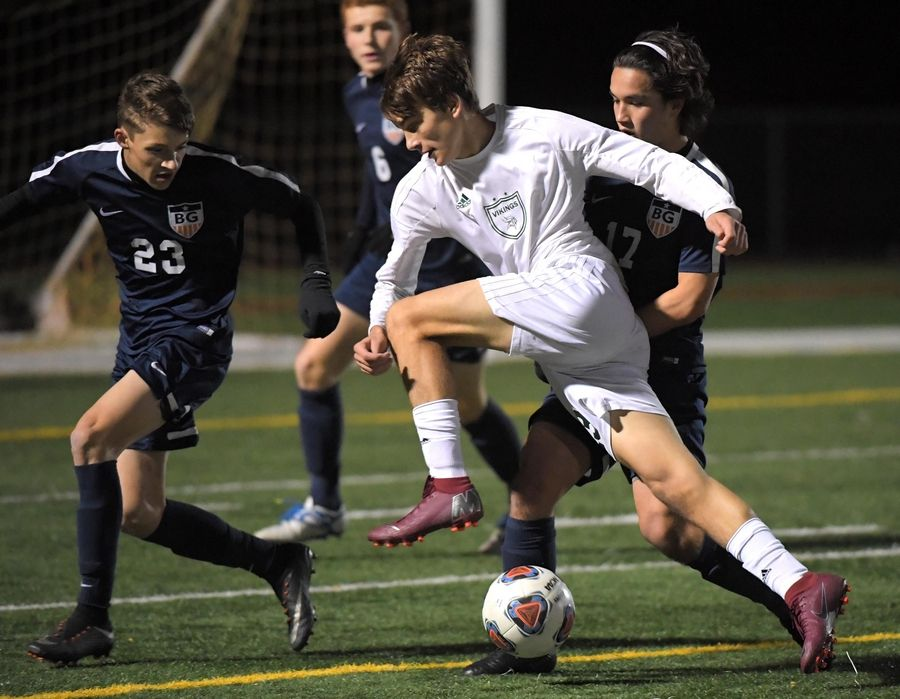 Fremd's Jake Scesniak keeps the ball away from Buffalo Grove's Ryan Kim, left, and Jack Coughlin during last year's Mid-Suburban League Soccer Bowl boys soccer game.