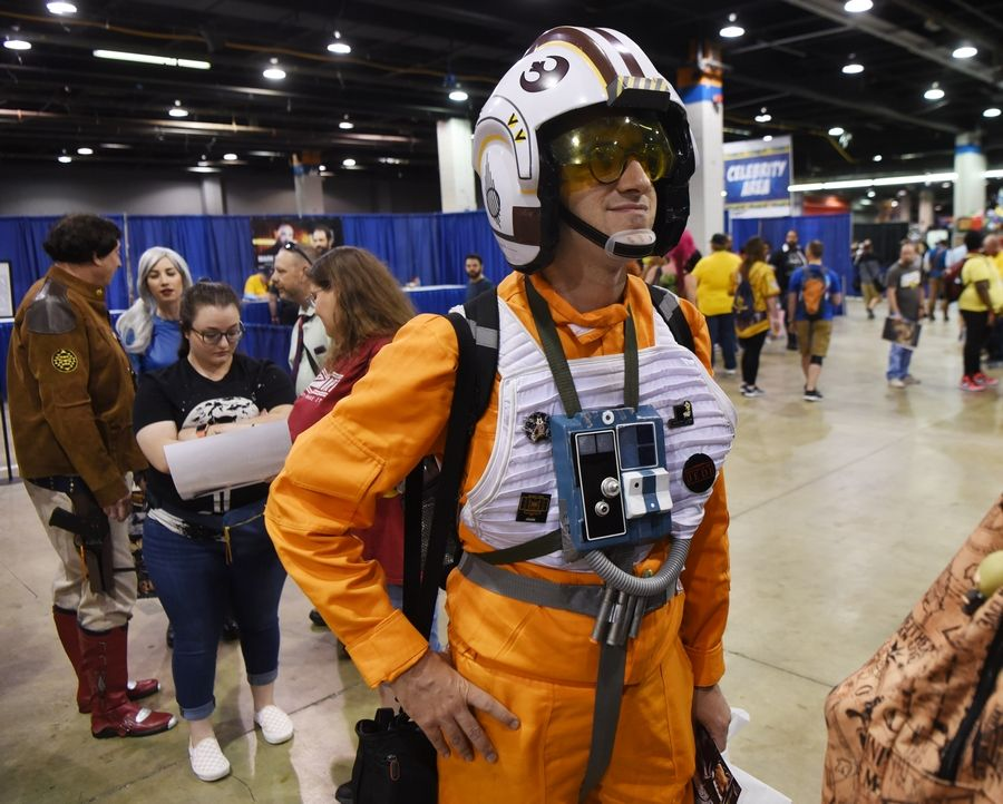 Waiting in line for celebrity autographs, Brian E. Mika of Arlington Heights is dressed as a Star Wars X-Wing Pilot, Red Squadron, during Wizard World at the Donald E. Stephens Convention Center in Rosemont Friday.