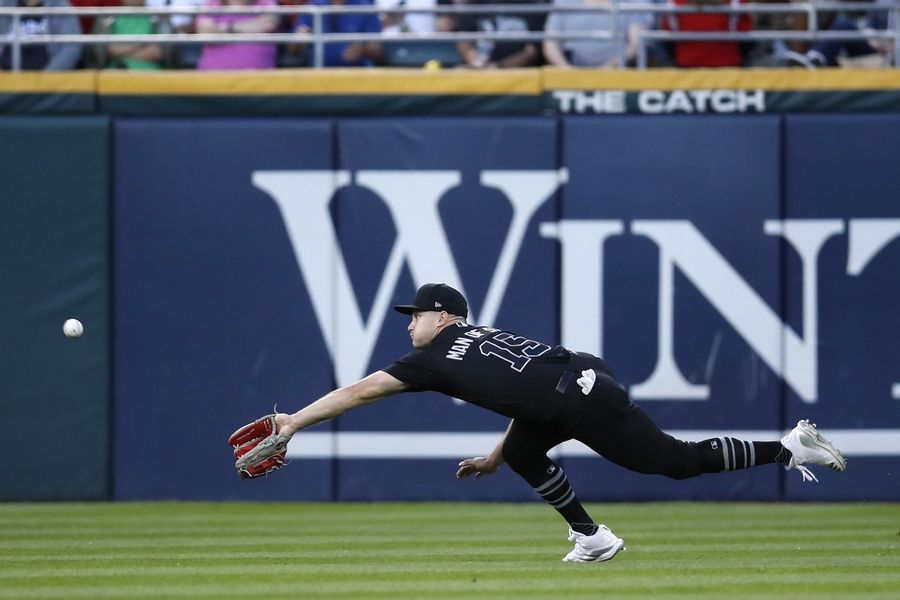 Chicago White Sox center fielder Adam Engel chases down a ball hit by Texas Rangers' Scott Heineman during the fifth inning of a baseball game Saturday, Aug. 24, 2019, in Chicago.