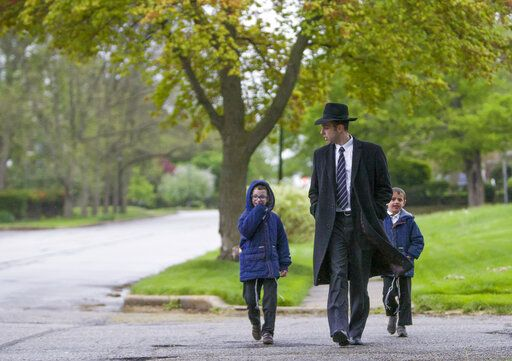 A jewish family walks along Miami Street on Saturday, May 11, 2019, in South Bend, Ind. (Santiago Flores/South Bend Tribune via AP)