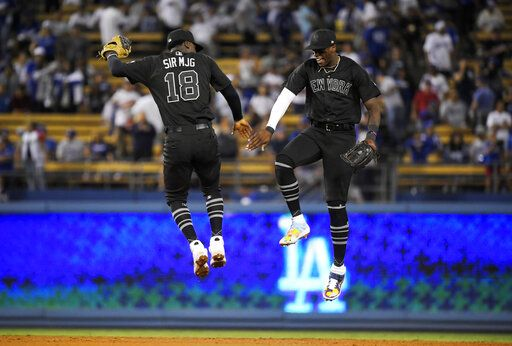 New York Yankees' Didi Gregorius, left, and Cameron Maybin celebrate after the Yankees defeated the Los Angeles Dodgers 10-2 in a baseball game, Friday, Aug. 23, 2019, in Los Angeles.