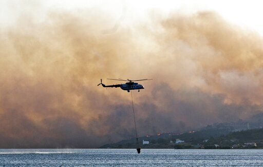 In this Saturday, Aug. 24, 2019 photo shows an helicopter fills its bucket with water during a wildfire near Pythagorio town on the eastern Greek island of Samos. Authorities evacuated two hotels and house the customers in an arena in the town of Pythagorio. Hot, dry weather and high winds helped fuel a total of 68 wildfires across Greece Saturday and the situation will remain dangerous Sunday.