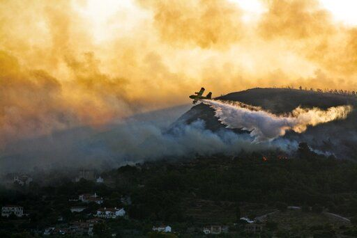In this Saturday, Aug. 24, 2019 photo shows an aircraft drops water over a wildfire near Pythagorio town on the eastern Greek island of Samos. Authorities evacuated two hotels and house the customers in an arena in the town of Pythagorio. Hot, dry weather and high winds helped fuel a total of 68 wildfires across Greece Saturday and the situation will remain dangerous Sunday.