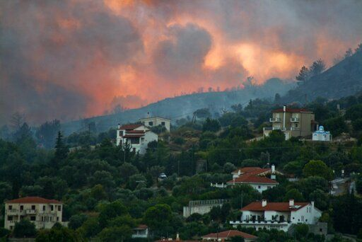 In this Saturday, Aug. 24, 2019 photo shows a wildfire burns a forrest near Pythagorio town on the eastern Greek island of Samos. Authorities evacuated two hotels and house the customers in an arena in the town of Pythagorio. Hot, dry weather and high winds helped fuel a total of 68 wildfires across Greece Saturday and the situation will remain dangerous Sunday.