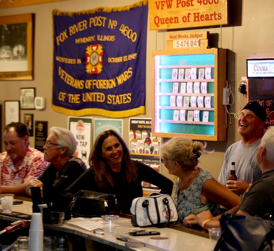 People visit near the game board before the conclusion of the Queen of Hearts drawing at McHenry VFW Post 4600 Tuesday. The winner known publicly only as Fred K. selected card 16, which turned out to be the coveted queen, and wins $2.74 million before taxes.