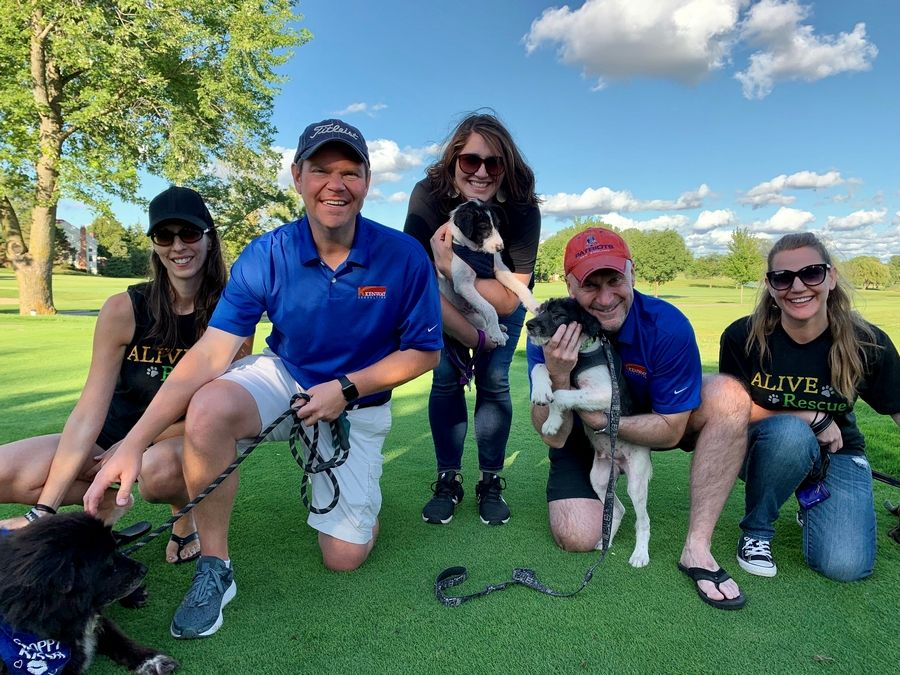 Kenway's Consulting's Matt Kueker (left) and Brian King (right) pose with some adorable adoptable pups and (from left to right) ALIVE Rescue's Kristen Gerali, Margo Strebig, and Hannah Nicolet at Kenway 's annual fundraiser for the local nonprofit. The money raised will help provide medical care for abandoned, abused & stray animals.
