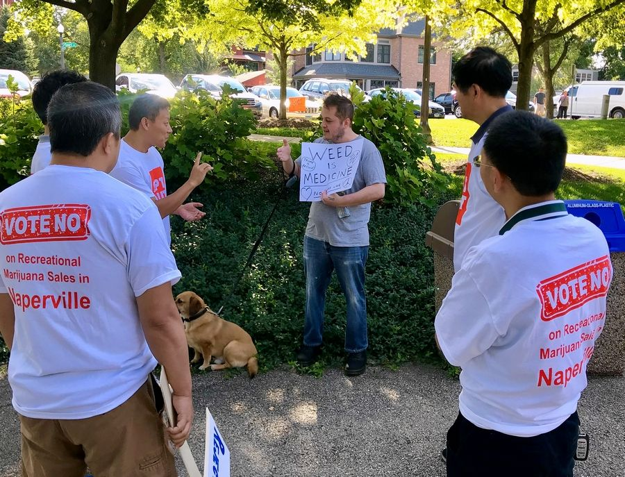 Naperville resident Dan Allen, middle, was the lone counterprotester at Saturday's rally in Naperville's Central Park organized by residents opposed to the city allowing recreational marijuana sales.