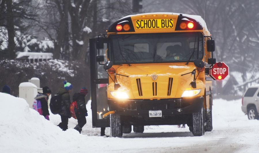 Lake County students board a bus this past winter on a snowy day. Libertyville-Vernon Hills Area High School District 128 educators are preparing an e-learning plan to teach students remotely on days classes are canceled due to snowstorms or other emergencies.