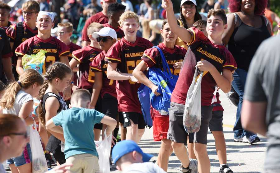Kids from various Schaumburg youth sports programs toss candy to children during Monday's Labor Day parade in Schaumburg.