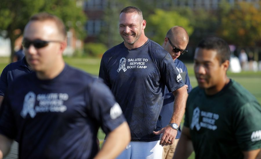 Brian Urlacher smiles as he works with Great Lakes Naval Station military service members during USAA's Salute to Service NFL Boot Camp Tuesday at Great Lakes Naval Station in North Chicago.