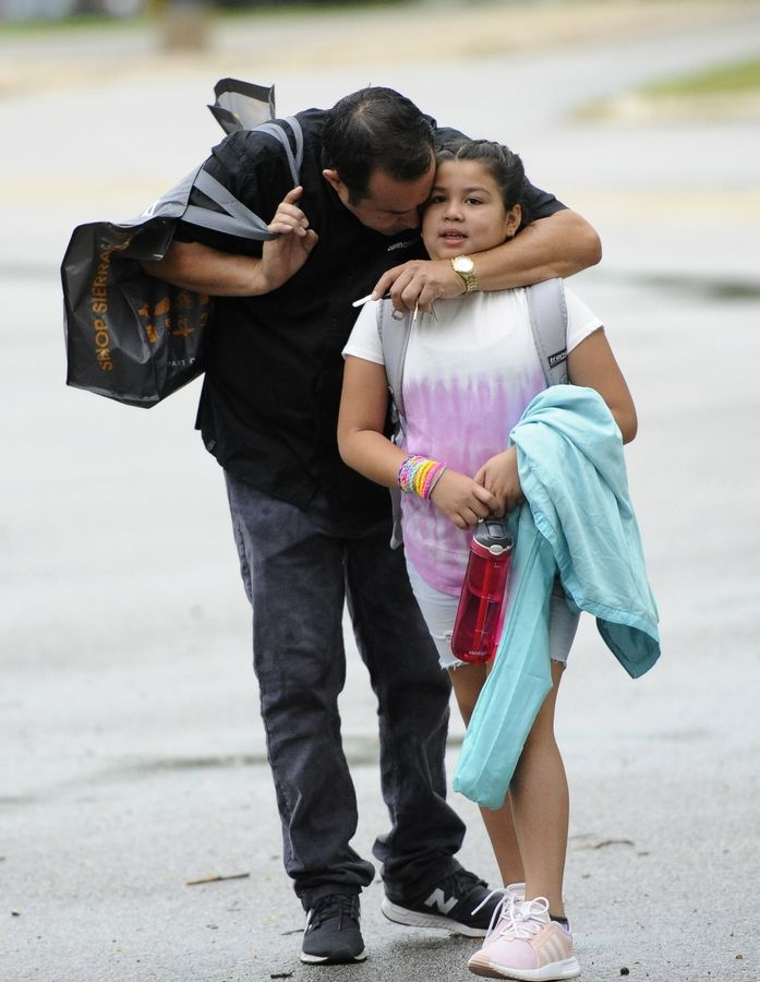 Ricardo Galvan gives his daughter Aliyah, 9, last-minute advice Tuesday before she heads off to her first day of school as a fourth grader at Riley Elementary School in Arlington Heights.