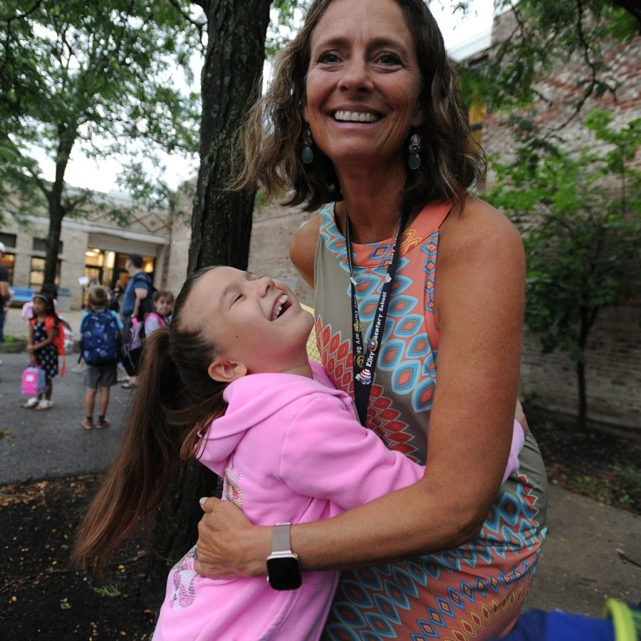 Second-grade teacher Debbie Allbright gets a hug Tuesday from Gabrijela Lukovic, 8, as students returned to classes at Riley Elementary School in Arlington Heights.