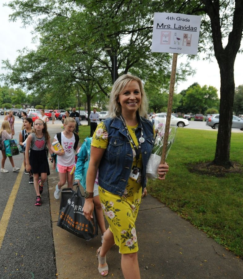 Holly Lavidas, who teaches fourth grade at Riley Elementary School in Arlington Heights, leads her students into the building Tuesday for the first day of school.