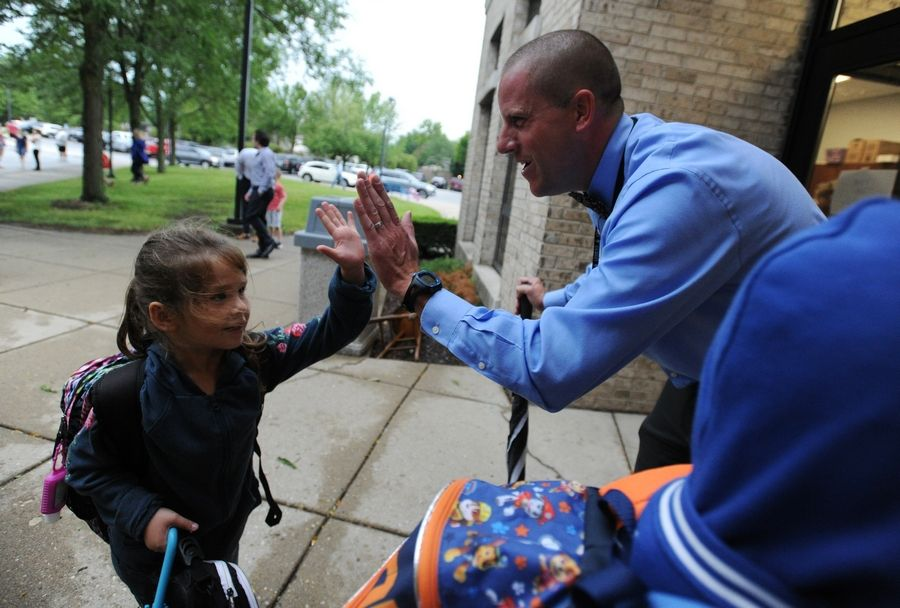 Principal Kevin Olsen greets students Tuesday on their first day back to school at Riley Elementary School in Arlington Heights.