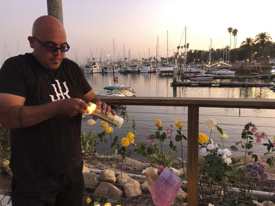 Orlando Aldana, 42, of Santa Barbara, bought 34 candles in honor of the victims to place at the growing memorial for those caught in the fire on the Conception boat, Monday, Sept. 2, 2019, in Santa Barbara, Calif. A fire raged through the boat carrying recreational scuba divers anchored near an island off the Southern California coast early Monday, leaving multiple people dead and hope diminishing that any of the more than two dozen people still missing would be found alive.