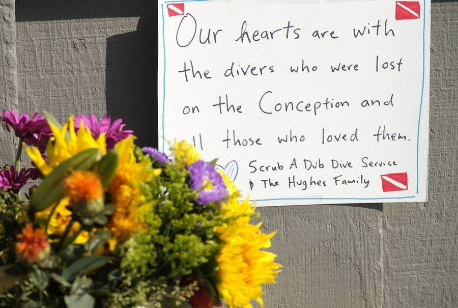 Flowers and messages are placed outside of the Sea Landing at Santa Barbara Harbor in Santa Barbara, Calif., Monday, Sept. 2, 2019. A fire raged through a boat carrying recreational scuba divers anchored near an island off the Southern California coast early Monday, leaving multiple people dead and hope diminishing that any of the more than two dozen people still missing would be found alive.