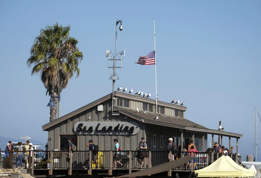 A U.S. flag flies at half-staff on the Sea Landing, where the Truth Aquatics office is situated, at Santa Barbara Harbor in Santa Barbara, Calif., Monday, Sept. 2, 2019. A boat carrying recreational scuba divers that caught a fire early Monday while anchored near Santa Cruz Island off the Southern California coast was owned and operated by Truth Aquatics.