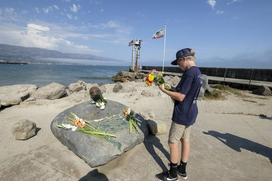 Colin Martz, an intern at Santa Barbara Sailing Center, places flowers at a dolphin statue at Santa Barbara Harbor in Santa Barbara, Calif., Monday, Sept. 2, 2019. A fire raged through a boat carrying recreational scuba divers anchored near an island off the Southern California coast early Monday, leaving multiple people dead and hope diminishing that any of the more than two dozen people still missing would be found alive.