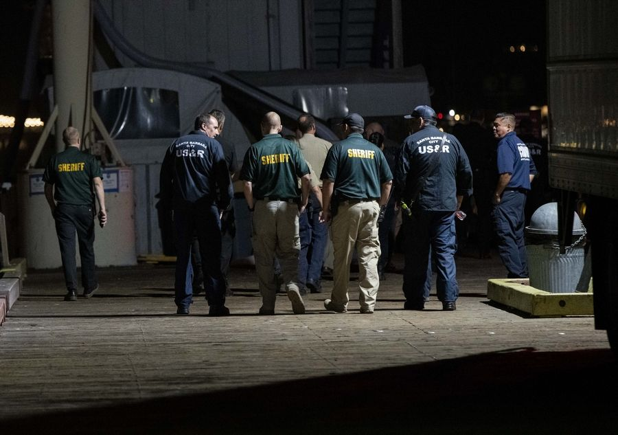 Local law enforcement along with search and rescue teams walk down a dock at Santa Barbara Harbor to help retrieve bodies of those who died in a diving boat fire Monday, Sept. 2, 2019, in Santa Barbara, Calif. A fire raged through a boat carrying recreational scuba divers anchored near an island off the Southern California coast early Monday, leaving multiple people dead and hope diminishing that any of the remaining people still missing would be found alive.