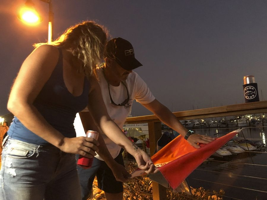 JJ Lambert, 38, and his fiancee, Jenna Marsala, 33, hang up a dive flag in remembrance of the victims of the Conception boat fire at a memorial site on Monday, Sept. 2, 2019, in Santa Barbara, Calif. A fire raged through the boat carrying recreational scuba divers anchored near an island off the Southern California coast early Monday, leaving multiple people dead and hope diminishing that any of the more than two dozen people still missing would be found alive.