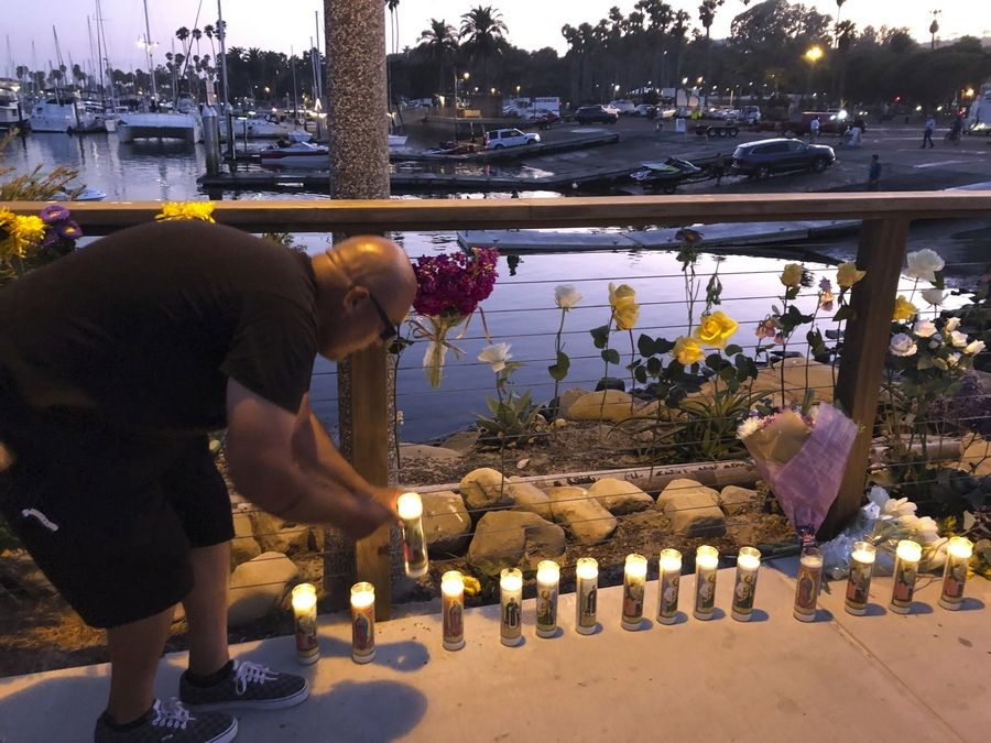 Orlando Aldana, 42, of Santa Barbara, lights candles in honor of the victims at the growing memorial for those caught in the fire on the Conception boat, Monday, Sept. 2, 2019, in Santa Barbara, Calif. A fire raged through the boat carrying recreational scuba divers anchored near an island off the Southern California coast early Monday, leaving multiple people dead and hope diminishing that any of the more than two dozen people still missing would be found alive.