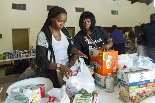 Volunteers Jazz Williams, 29, left, and Jodye Scavella, 47, organize donated goods for those affected by Hurricane Dorian in the Bahamas, at Christ Episcopal Church in Miami, Tuesday, Sept. 3, 2019. Members of two historically black churches are sorting and preparing the supplies to be flown to the hurricane-ravaged islands of Abaco and Grand Bahama.