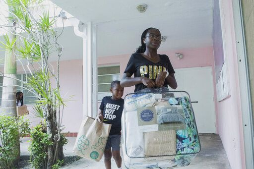 Volunteers Sanai Clark, 14, and Elliot Mirutil, 7, bring items to be donated to the Bahamas at Christ Episcopal Church in Miami, Tuesday, Sept. 3, 2019. In the wake of Hurricane Dorian, the church has organized items to be sent to the island nation via seaplane.