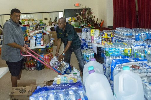 Ryan Smith, 60, left, and Hiram Williams, 71, stock an auditorium with goods slated to be sent to the Bahamas at Christ Episcopal Church in Miami, Tuesday, Sept. 3, 2019. South Florida residents spared from Hurricane Dorian's wrath are donating relief supplies to relatives in the Bahamas. Droves of Floridians turned out Tuesday to share cans of food, water bottles and boxes of diapers.