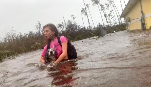 Julia Aylen wades through waist deep water carrying her pet dog as she is rescued from her flooded home during Hurricane Dorian in Freeport, Bahamas, Tuesday, Sept. 3, 2019. Practically parking over the Bahamas for a day and a half, Dorian pounded away at the islands Tuesday in a watery onslaught that devastated thousands of homes, trapped people in attics and crippled hospitals. Julia Aylen is the daughter of Photojournalist Tim Aylen, author of this photo.