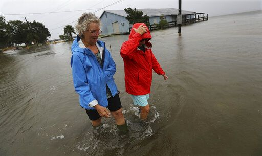 Jen Fabrick, left, and Anne Herring, right, walk through flood waters covering St. Mary's Street at Langs Marina near their homes while Hurricane Dorian passes by on Wednesday, Sept. 4, 2019, in St. Mary's, Ga. (Curtis Compton/Atlanta Journal-Constitution via AP)