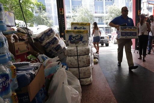 A Miami Fire Rescue official carries donated supplies at a fire station in Miami for those affected by Hurricane Dorian in the devastated Bahamian islands of Abaco and Grand Bahama, Wednesday, Sept. 4, 2019. Local churches are also accepting supplies in a relief effort spearheaded by descendants of some of Miami's earliest settlers from the Bahamas.
