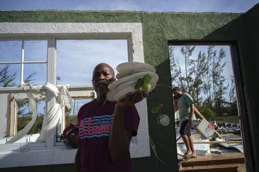Mister Bolter recovers dishes from his son's home, destroyed by Hurricane Dorian in Pine Bay, near Freeport, Bahamas, Wednesday, Sept. 4, 2019. Rescuers trying to reach drenched and stunned victims in the Bahamas fanned out across a blasted landscape of smashed and flooded homes Wednesday, while disaster relief organizations rushed to bring in food and medicine.