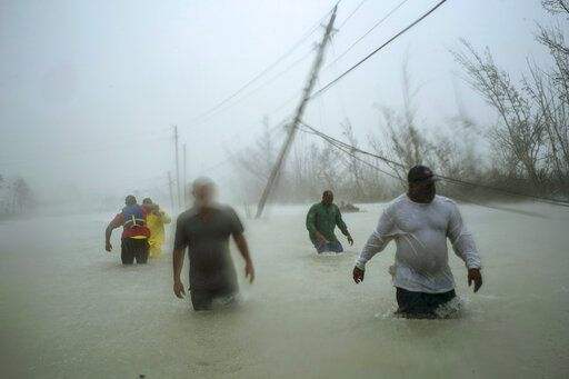 Volunteers walk under the wind and rain from Hurricane Dorian through a flooded road as they work to rescue families near the Causarina bridge in Freeport, Grand Bahama, Bahamas, Tuesday, Sept. 3, 2019. The storm's punishing winds and muddy brown floodwaters devastated thousands of homes, crippled hospitals and trapped people in attics.