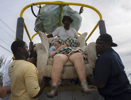 Sitting in her home's lounger, Virginia Mosvold, 84, is lowered from a truck by volunteers after being rescued from her flooded home on Ol' Freetown Farm farm in the aftermath of Hurricane Dorian before being taken to the hospital on the outskirts of Freeport, Bahamas, Wednesday, Sept. 4, 2019. Rescue crews in the Bahamas fanned out across a blasted landscape of smashed and flooded homes trying to reach drenched and stunned victims of Hurricane Dorian and take the full measure of the disaster.