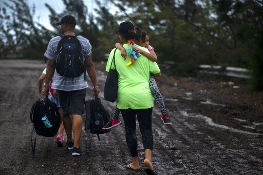 A family walks on a road after being rescued from the flood waters of Hurricane Dorian, near Freeport, Grand Bahama, Bahamas, Tuesday Sept. 3, 2019. They were rescued by volunteers who drove a bus into the flood waters to pick them up.