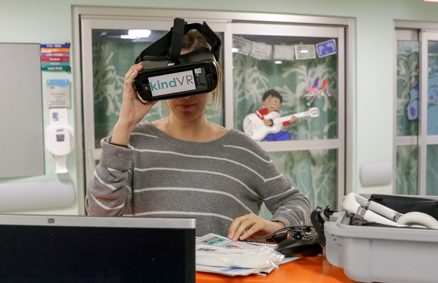 Child life specialist Kristen Medica tests a pair of virtual reality goggles for a child to use at Edward Hospital in Naperville.