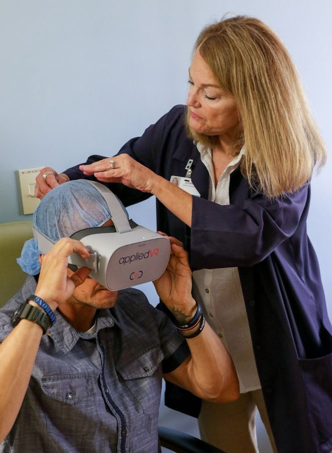 Barbara McDonnell, an Edward Hospital volunteer in oncology, helps her son-in-law Chris Kudla begin a virtual reality therapy session to help ease the pain of his chemotherapy to fight Stage IV papillary kidney cancer. Kudla, 47, said the goggles offer a welcome escape from the reality of cancer treatment.