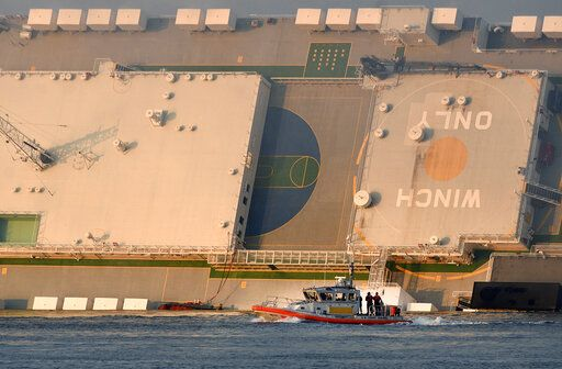 Rescuers pull 3 from capsized cargo ship, 1 still trapped