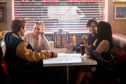 "This image released by The CW shows, from left, KJ Apa as Archie Andrews, Lili Reinhart as Betty Cooper, Cole Sprouse as Jughead Jones, and Camila Mendes as Veronica Lodge, in a scene from ""Riverdale."" The cast and creators of ""Riverdale� will receive an award from a gay rights education group for the show's portrayal of LGBTQ relationships in a high school setting.  (Diyah Pera/The CW via AP)"