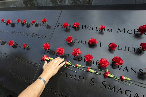 Norma Molina, of San Antonio, Texas, leaves flowers by the names of firefighters from Engine 33 at the September 11 Memorial, Monday, Sept. 9, 2019, in New York. Her boyfriend Robert Edward Evans, a member of Engine 33, was killed in the north tower of the World Trade Center on Sept. 11, 2001.
