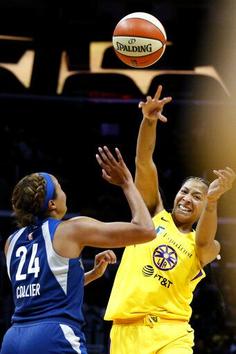 Los Angeles Sparks' Candace Parker, right, passes the ball while defended by Minnesota Lynx's Napheesa Collier during the second half of a WNBA basketball game in Los Angeles, Sunday, Sept. 8, 2019.