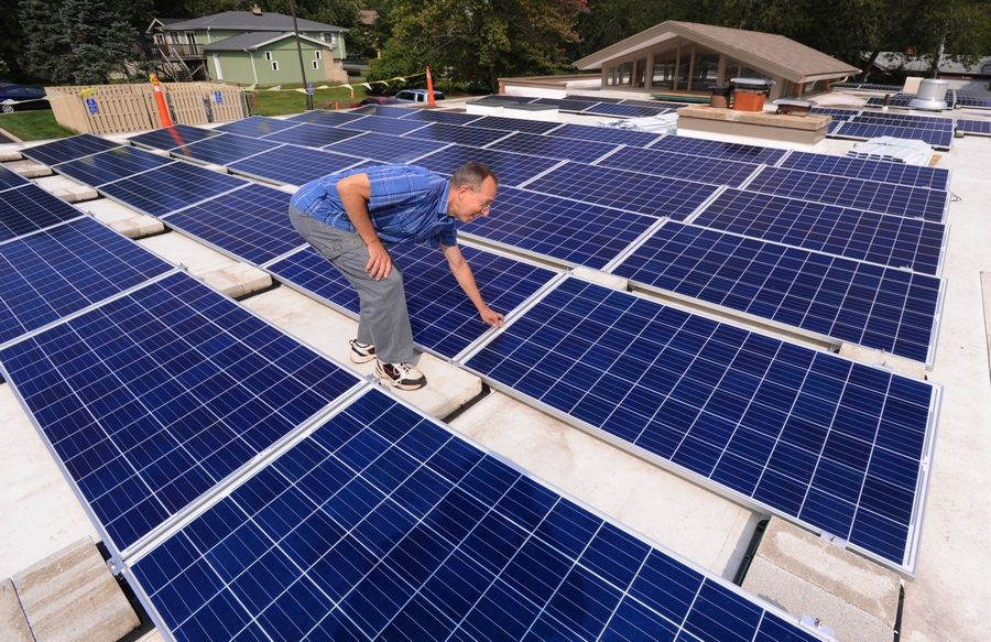 Our Saviour's Lutheran Church Operations Officer Jim Valentine inspects some of the 272 solar panels dotting the rooftop of the Arlington Heights church.