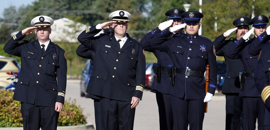 Police officers salute during Aurora's Sept. 11 observance last year.